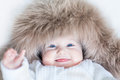 Funny cute baby girl wearing huge winter hat with big blue eyes a Stock Photo