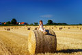 Funny cute little girl posing on the haystack in summer field Royalty Free Stock Photo