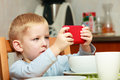 Funny dirty boy child kid taking photo with red mobile phone indoor at home technology generation Stock Image
