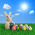 Funny easter rabbit with eggs on a green grass Royalty Free Stock Image