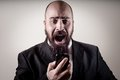 Funny elegant bearded man screaming on the phone vignetting background Stock Image