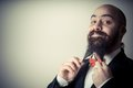 Funny elegant bearded man touching beard on vignetting background Royalty Free Stock Images