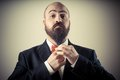 Funny elegant bearded man touching beard on vignetting background Royalty Free Stock Photo