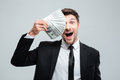 Funny excited young businessman covered one eye with money Royalty Free Stock Photo