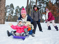 Funny family is sledging in winter landscape four kids with mother Stock Photo