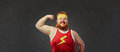 Funny fat man in sports clothes shows a hand with muscles biceps Royalty Free Stock Photo