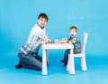 Funny father and little son competing in arm wrestling on blue background Stock Photo