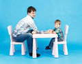 Funny father and little son competing in arm wrestling on blue background Royalty Free Stock Photos