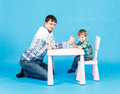 Funny father and little son competing in arm wrestling on blue background Royalty Free Stock Image
