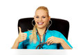 Funny female doctor or nurse sitting behind the desk with stethoscope Royalty Free Stock Photo