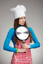 Funny female portrait klutz in the kitchen of a woman chef s hat with pan her hands gray background Royalty Free Stock Photos
