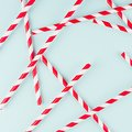 Funny festive bright abstract background - striped red cocktail straws on pastel candy mint color backdrop, pattern, square. Royalty Free Stock Photo