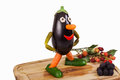 Funny figure carved out of an aubergine with deco fruits on a wooden board isolated Stock Photo