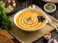 Funny food for Halloween. Pumpkin puree soup, spider web, dark old wooden table, side view. Royalty Free Stock Photo