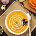 Funny food for Halloween. Pumpkin puree soup, spider web, dark old wooden table, top view. Royalty Free Stock Photo