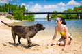 Funny game of a young woman and dog playing on the beach Stock Photography