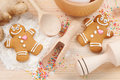 Funny gingerbread men flour rolling pin spoon and ginger on kitchen table Stock Images