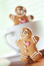 Funny gingerbread men play about a cup Royalty Free Stock Images