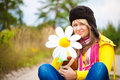 Funny girl in cap with ear flaps and flower Royalty Free Stock Photography