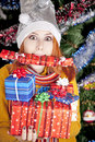 Funny girl in christmas cap with gift boxes Stock Image