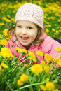 Funny girl in dandelions Stock Photography