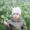 Funny girl with down syndrome in the mouth pulls dandelions Stock Photo