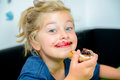 Funny girl eating bread roll with marmelade Royalty Free Stock Photo