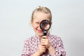 Funny girl explores magnifying glass Royalty Free Stock Images