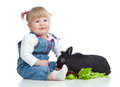 Funny girl feeding a rabbit with vegetables Royalty Free Stock Images