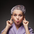 Funny girl grimaces in a hat for a shower and a towel wearing bathing cap Royalty Free Stock Photography