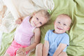 Funny girl with little brother happy kids sister and relaxing on a bed Royalty Free Stock Image
