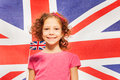 Funny girl with little flag against British banner Royalty Free Stock Photo