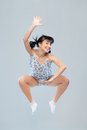 Funny girl in pajamas jumping for happiness is studio Stock Image