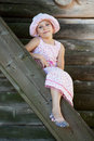 Funny girl in panama sits on a  ladder Royalty Free Stock Photography