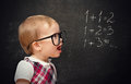 Funny girl pupil solves arithmetic examples baby on blackboard Stock Photos