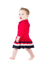 Funny girl in a red dress learning to stand