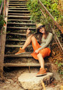 Funny girl show tongue have fun on the old wooden stairs outdoor Stock Photos