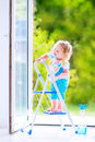 Funny girl washing a window cute laughing curly toddler big with squeegee in beautiful white living room with door into the garden Stock Photography