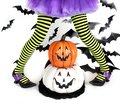 Photo : Funny green black Striped legs of a little girl with halloween costume of a witch with witch shoes and smiley halloween pumpkin on shoes woman