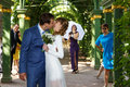 Funny groom kissing bride in wedding dress under the arch