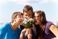 Funny groom with mother and sister eat bouquet of flowers