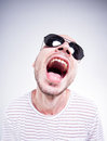 Funny guy wearing sun glasses screaming fish eye shot studio Royalty Free Stock Photos
