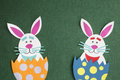 Funny handmade cartoon rabbits placed inside eggs with copyspace