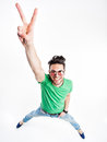 Funny handsome man with hipster glasses showing victory and smiling wide angle shot Royalty Free Stock Image