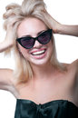 Funny happy girl with sun glasses young blond woman model wearing stylish black top big silk bow bright pink lipstick having fun Royalty Free Stock Image