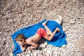 Funny smiling healthy little boy lying on blue towel on beach in hot summer day Royalty Free Stock Photo