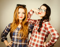 Funny hipster girls making faces wearing plaid shirt and retro glasses pretending to wear a mustache retro filter effect added Royalty Free Stock Photos