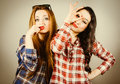 Funny hipster girls making faces weraing plaid shirt pretending to wear a mustache and glasses retro filter effect added Stock Photos