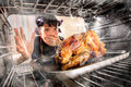 Funny housewife perplexed and angry loser is destiny overlooked roast chicken in the oven so she had scorched view from the inside Royalty Free Stock Photography
