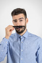 Funny immature guy holding plastic black comb to imitate his fake mustache desaturated portrait over gray studio background with Stock Photos